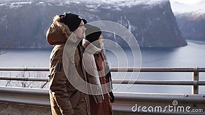 Turyści w zimowych płaszczach i czarnych kapeluszach chodzących w zwolnionym tempie po długiej drodze przez wieś w kierunku śnież zbiory