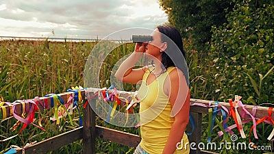 Turystka na pokładzie obserwacyjnym bada celowniki lornetką zdjęcie wideo