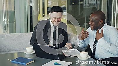 Två affärsmän som talar ang som skrattar i modernt kafé Affärskollegor som har gyckel och skojar se bärbara datorn lager videofilmer