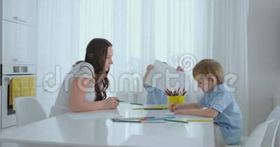 Två barn av pojkeattraktion med hans moder som sitter i köket lycklig utgångspunkt för familj stock video