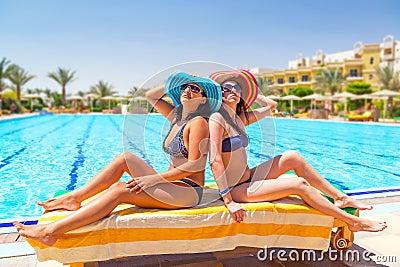 Två brunbrända flickor på simbassängen