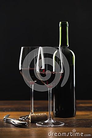 Två exponeringsglas av rött vin och flaskan