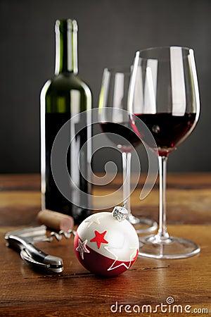 Två exponeringsglas av rött vin och julbaubel