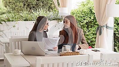 Två flickor diskuterar nytt affärsprojekt, medan ha lunch på kaféultrarapiden lager videofilmer