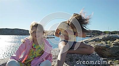 Två små flickor spelar bland det kust- vaggar på stranden arkivfilmer