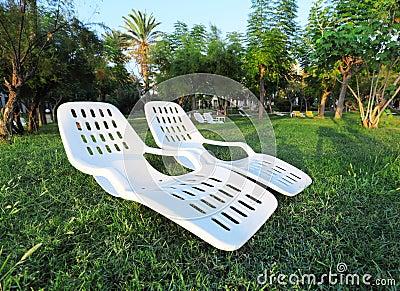 Två tomma plastic stolar i park. Rekreation