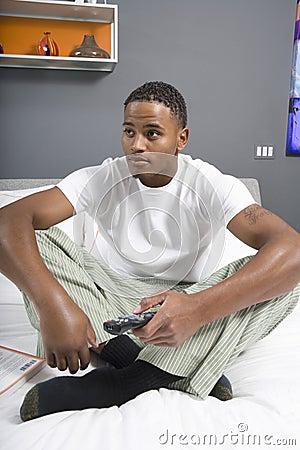 Молодой человек смотря TV в спальне