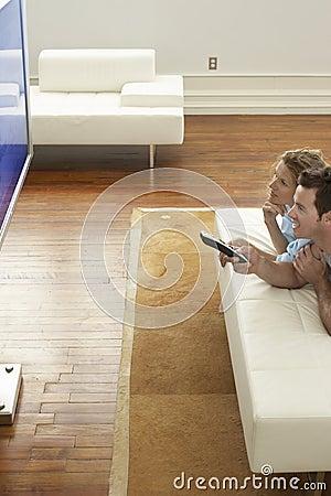 TV πλάσματος προσοχής ζεύγους στο σπίτι
