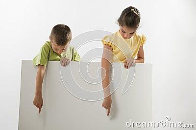 Två barn som rymmer ett blankt tecken