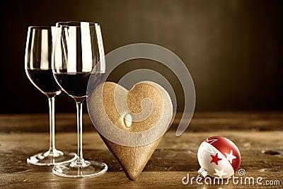 Två exponeringsglas av rött vin, pepparkaka och julbaubel