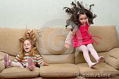 Två liten flicka som hoppar på sofaen