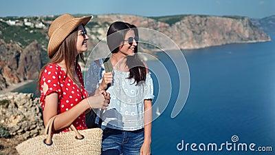 Twee aantrekkelijk toevallig reismeisje die mooi zeegezicht vanaf bovenkant van berg middelgroot schot bewonderen stock video