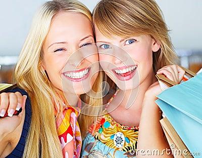 Twee aantrekkelijke gelukkige meisjes die uit winkelen