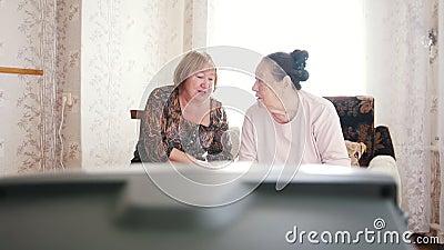 Twee bejaarden die op TV letten, en aan elkaar becommentariëren spreken stock videobeelden