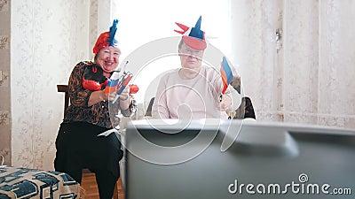 Twee bejaarden die op TV in Russische toebehoren letten en gelukkig Russische vlaggen golven stock footage