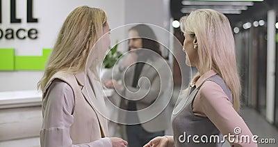 Twee blanke vrouwen die praten, naar de man in het Midden-Oosten kijken op de achtergrond, en lachen Vrouwen flirten met stock video