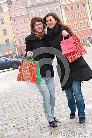 Twee gelukkige meisjes die fter winkelen