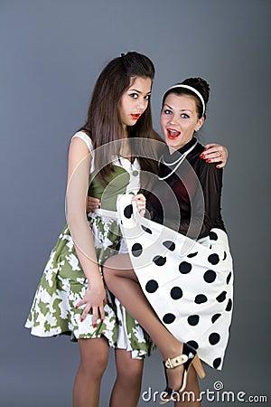 Twee gelukkige retro-gestileerde meisjes