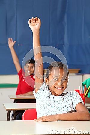 Twee het glimlachen jonge wapens van schoolkinderen die in c worden opgeheven