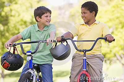Twee jonge jongens op fietsen die in openlucht glimlachen
