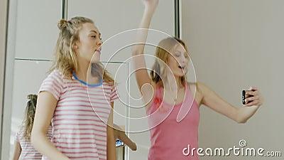 Twee jonge meisjestienerjaren leren grappige te dansen dans Neem een blik bij het mobiele telefoonscherm en herhaal de beweging stock videobeelden