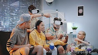 Twee jonge mensen die online spel in virtuele werkelijkheidsglazen spelen, één kerel wint de slag stock footage