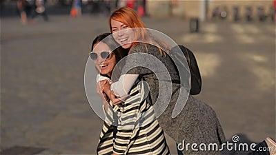 Twee jonge vrouwelijke vrienden die van meisjesvrienden op de rug op vakantie geven die en bij de straat, mooie stad lacht loopt stock videobeelden