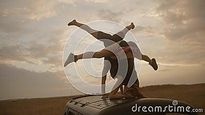 Twee jonge vrouwen met perfect saldo in handstand en headstand positie stock footage