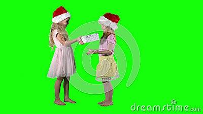 Twee kleine meisjes ruilen hun cadeautjes voor kerstmis Chromasleutel stock footage