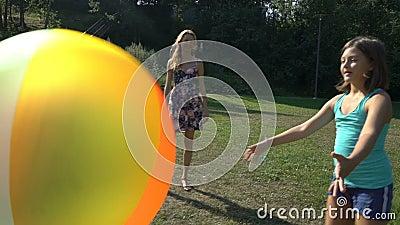 Twee leuke meisjes van verschillende leeftijden hun moeder spelen met een grote kleurrijke regenboog opblaasbare bal stock video