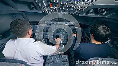 Twee loodsen die een vliegtuig in een simulator landen, achtermening stock videobeelden