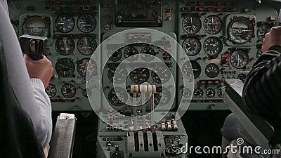 Twee loodsen vliegen een vliegtuig, zittend bij de controles stock footage