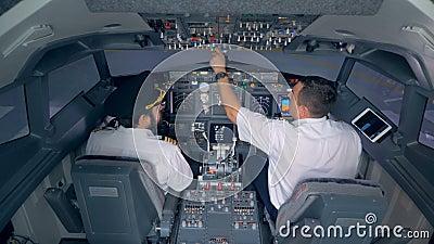 Twee loodsen zitten in een vliegtuigcabine en bespreken iets stock video