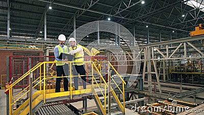 Twee mannen werken in een baksteenfabriek en controleren machines Werknemers in de fabriek stock videobeelden