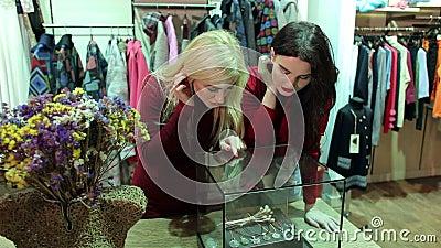 Twee meisjes die toebehoren en juwelen op de teller in een kleding bekijken slaan op stock video