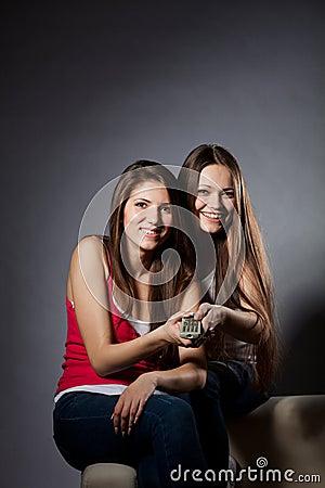 Twee meisjes letten op TV