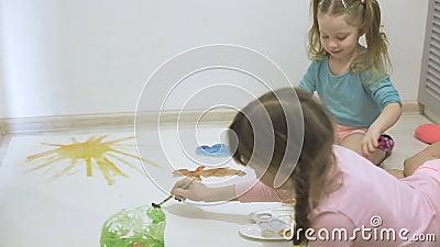 Twee meisjes verven met waterverf en penselen op een groot tekenpapier op de vloer, de gezamenlijke creativiteit van kinderen stock footage