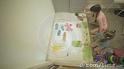 Twee meisjes verven met waterverf en penselen op een groot tekenpapier op de vloer, de gezamenlijke creativiteit van kinderen stock videobeelden