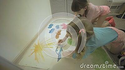 Twee meisjes verven met waterverf en penselen op een groot tekenpapier op de vloer, de gezamenlijke creativiteit van kinderen stock video