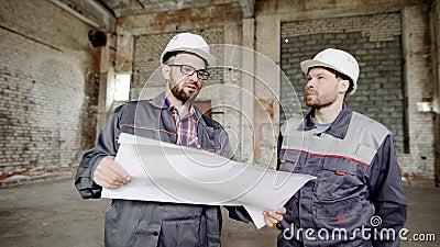 Twee mensen, die de bouwers in een beschermende helm op hun hoofden en speciale kleren de fabriek bouw bekijken stock videobeelden