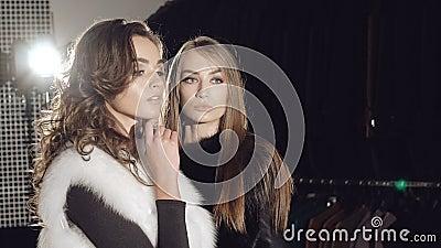 Twee modellentribunes stellen binnen in bontjassen in modieuze rijke boutique stock videobeelden