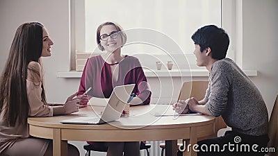 Twee mooie positieve Kaukasische meisjes spreken aan de Japanse mens bij een baangesprek door de lijst in modern gezond bureau stock video