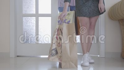 Twee niet erkende modieuze meisjes naar huis achter met hun aankopen na het winkelen Slechts zijn de benen en het winkelen de zak stock footage