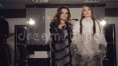 Twee rijke dames die in bontjassen in modieuze boutique stellen stock video
