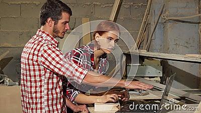Twee timmerlieden die laptop met behulp van op hun workshop terwijl het maken van meubilair stock videobeelden