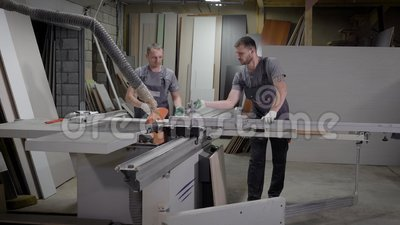 Twee timmerlieden werken in een schrijnwerkerswinkel in installatie, scherpe spaanplaat voor het voorbereidingen treffen voor het stock footage