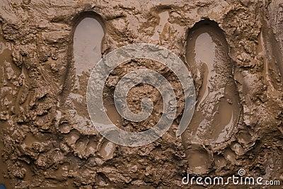 Twee voetafdrukken op natte modder
