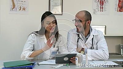 Twee vrolijke artsen die positieve videovraag via tablet hebben stock footage
