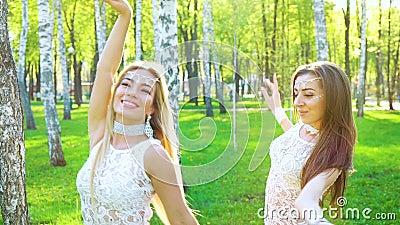 Twee vrouwen in van glamourkostuums en toebehoren dans in zonovergoten berkbosje stock video