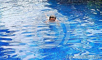 Tween white girl swimming in a pool.